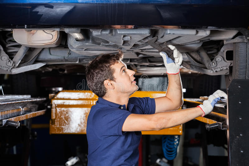 Carro levantado Using Wrench Underneath do mecânico imagens de stock