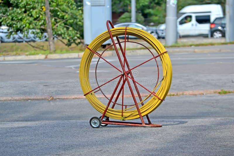 Carro metálico amarelo da bobina com cabo ótico para telecomunicações, diversidade do Internet, imagens de stock