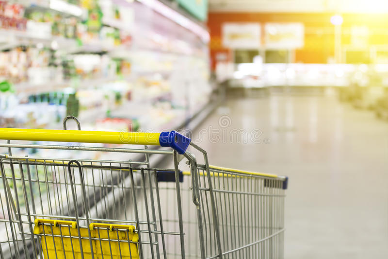 Carro na mercearia Abstraia a foto borrada da loja com o trole no fundo do bokeh do armazém fotos de stock
