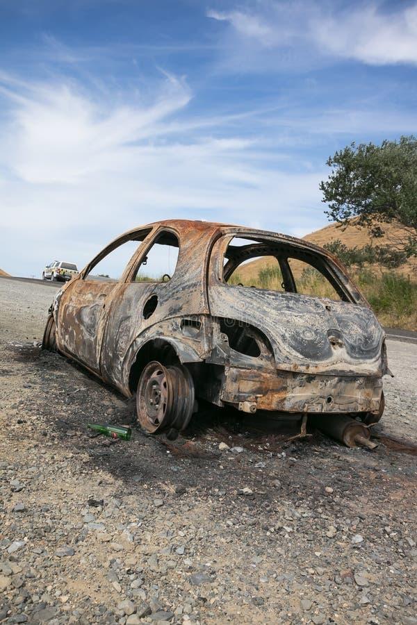 Carro para fora queimado no lado de uma estrada fotografia de stock