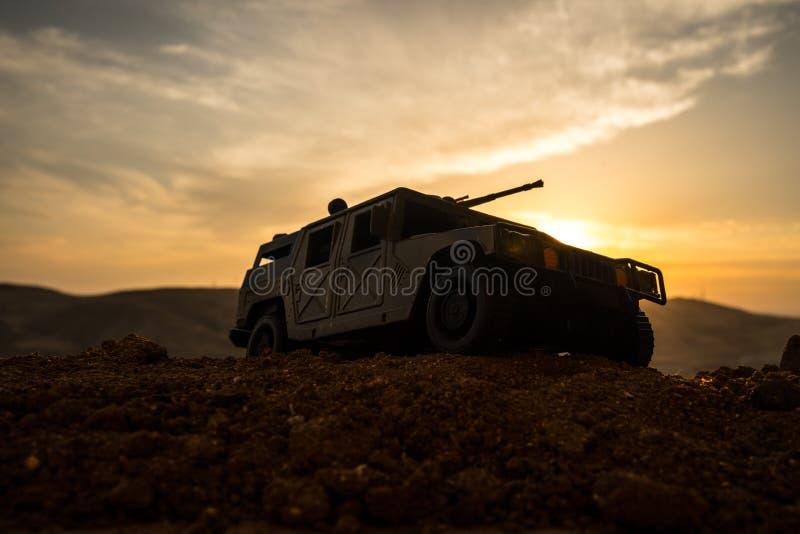 Carro-patrulha militar no fundo do por do sol Conceito da guerra do exército Silhueta de veículo blindado com a arma na ação deco imagens de stock royalty free
