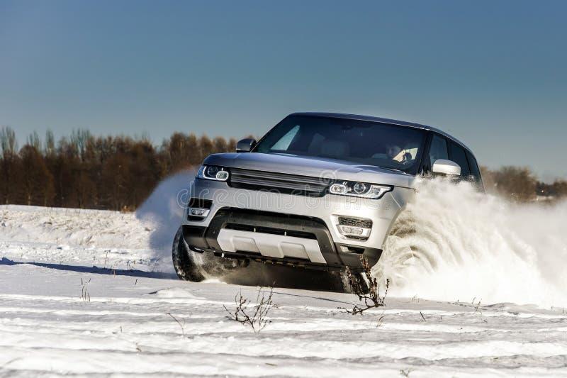 Carro poderoso do offroader 4x4 que corre no campo de neve imagens de stock royalty free