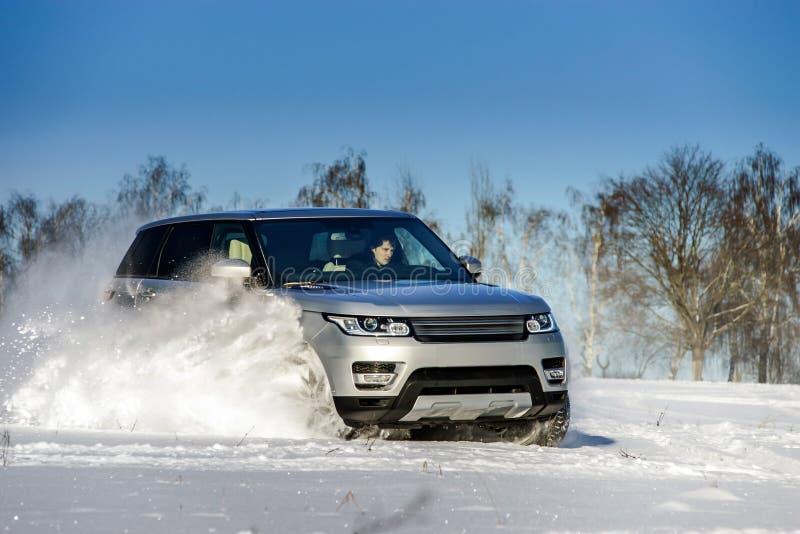 Carro poderoso do offroader 4x4 que corre no campo de neve foto de stock