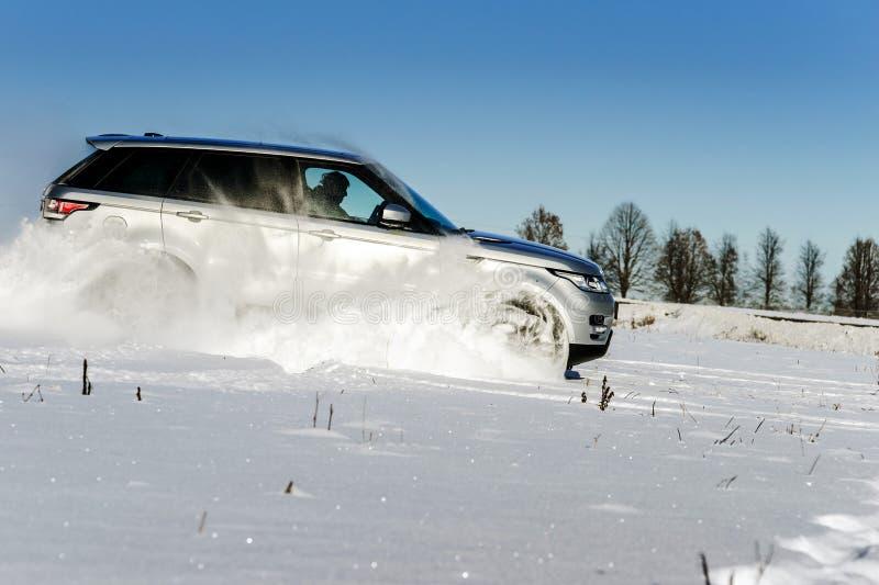 Carro poderoso do offroader 4x4 que corre no campo de neve imagens de stock