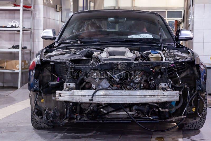 Carro preto desmontado na oficina preparada para o reparo: equipamento removido, interno da parte frontal, da capa e do amorteced fotografia de stock