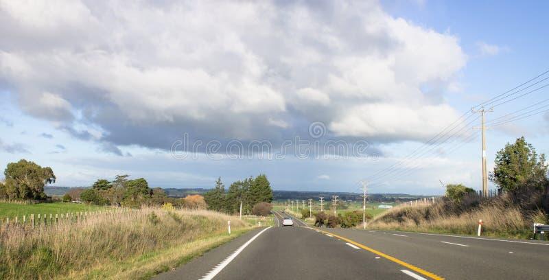 Carro que viaja ao longo de uma estrada rural em Nova Zelândia foto de stock