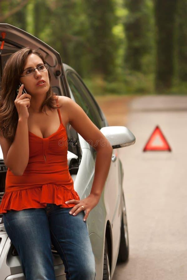 Carro quebrado - atendimentos da mulher nova para o auxílio fotografia de stock royalty free