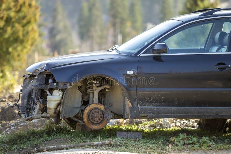 Carro quebrado oxidado deixar para lá velho do lixo após o acidente do impacto sem as rodas nos selos de madeira cobertos com a n fotografia de stock