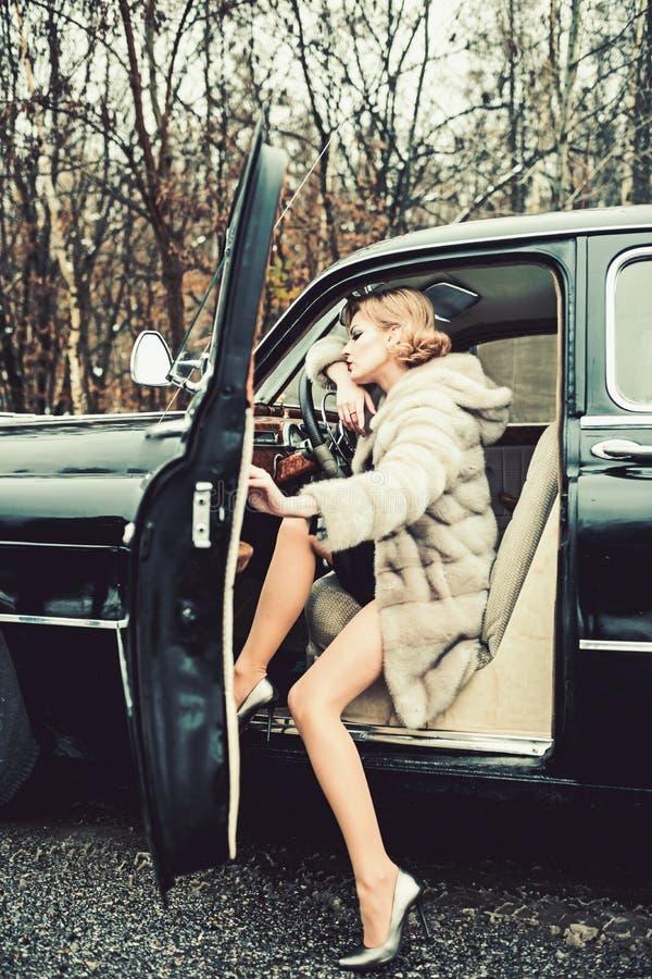 Carro retro e repara??o de autom?veis da cole??o pelo motorista Menina de chamada no carro do vintage Mulher 'sexy' no casaco de  imagens de stock