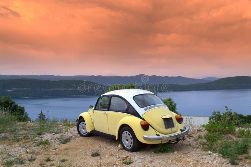 Carro retro na costa do nascer do sol fotos de stock royalty free