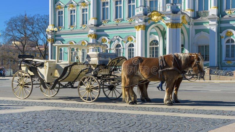 Carro retro viejo delante del museo de ermita del palacio del invierno en cuadrado del palacio en St Petersburg, Rusia Viejo hist foto de archivo libre de regalías