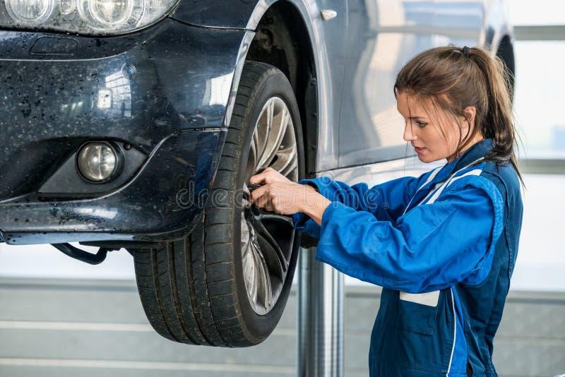 Carro suspendido Changing Tire From fêmea do mecânico imagem de stock royalty free