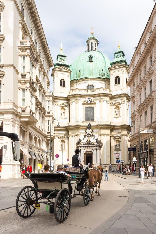 Carro traído por caballo en la iglesia de Peterskirche en Viena imagenes de archivo
