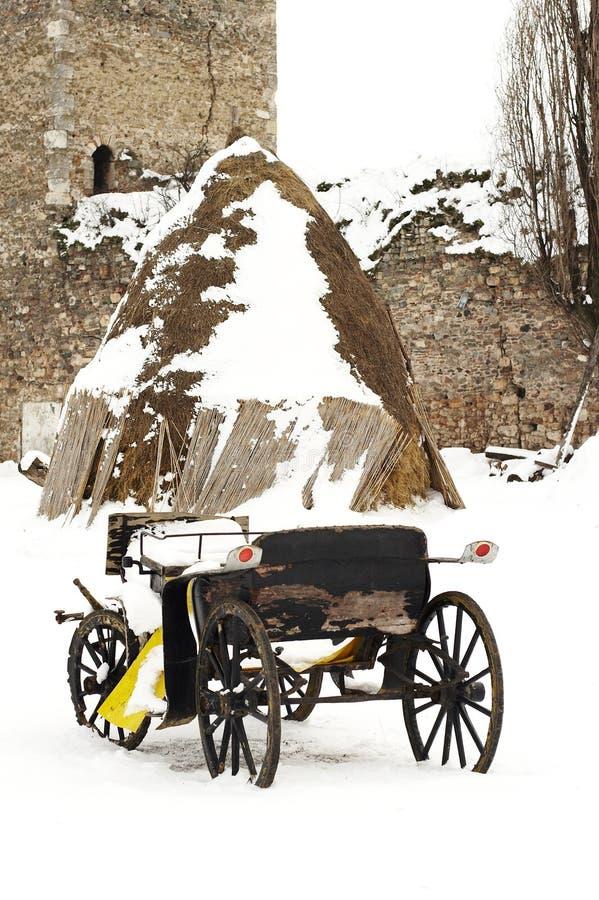 Carro traído por caballo viejo en la nieve imagenes de archivo