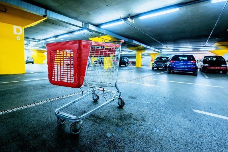 Carro vacío abandonado en el estacionamiento del garaje de subterráneo de la alameda de compras foto de archivo