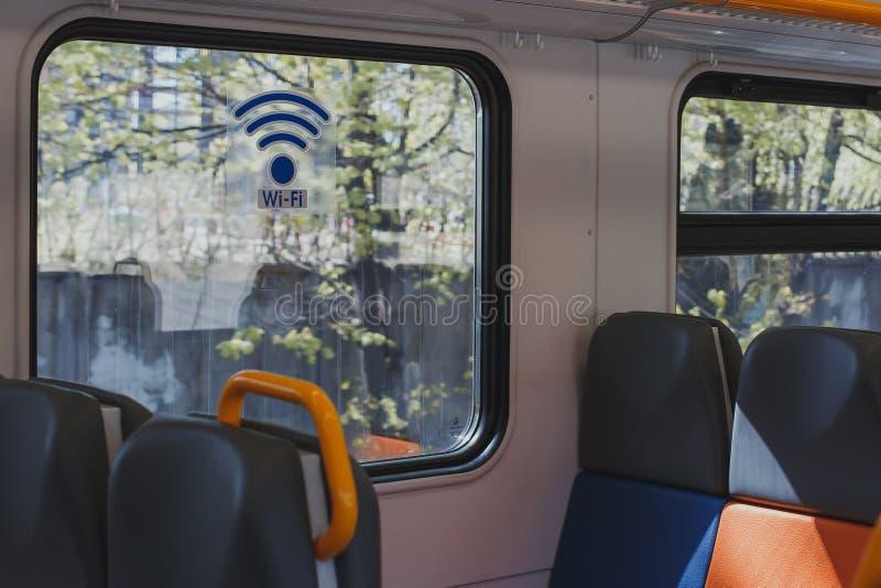Carro vacío del tren con los asientos multicolores y una etiqueta engomada en el WI-FI de la ventana imagenes de archivo
