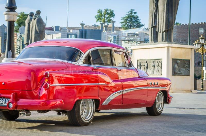 Carro velho do temporizador do vintage movente bonito dos anos sessenta em um centro da cidade imagem de stock