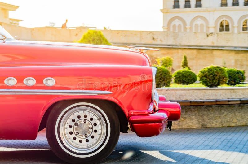 Carro velho do temporizador do vintage vermelho bonito dos anos sessenta em um centro da cidade imagens de stock