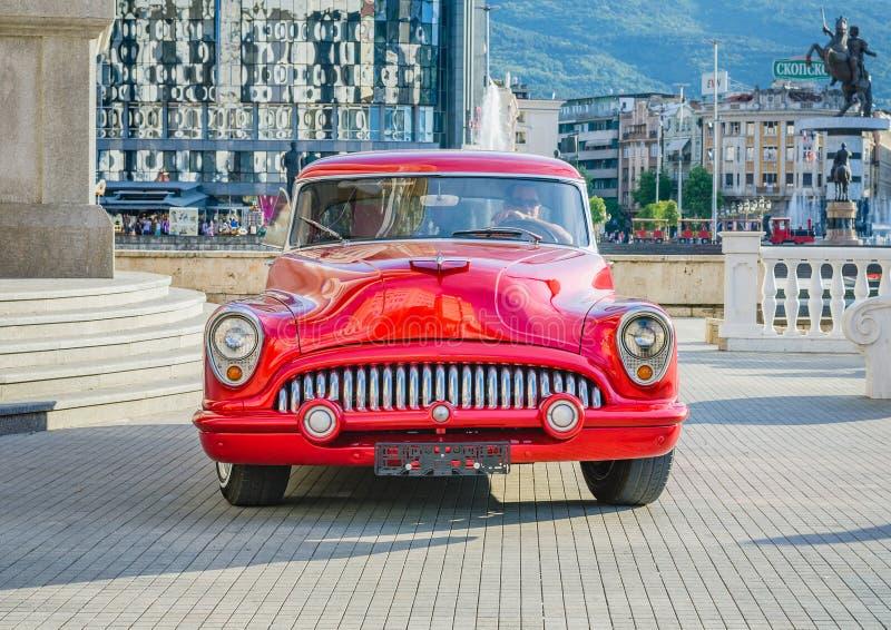 Carro velho do temporizador do vintage vermelho bonito dos anos sessenta em um centro da cidade fotos de stock