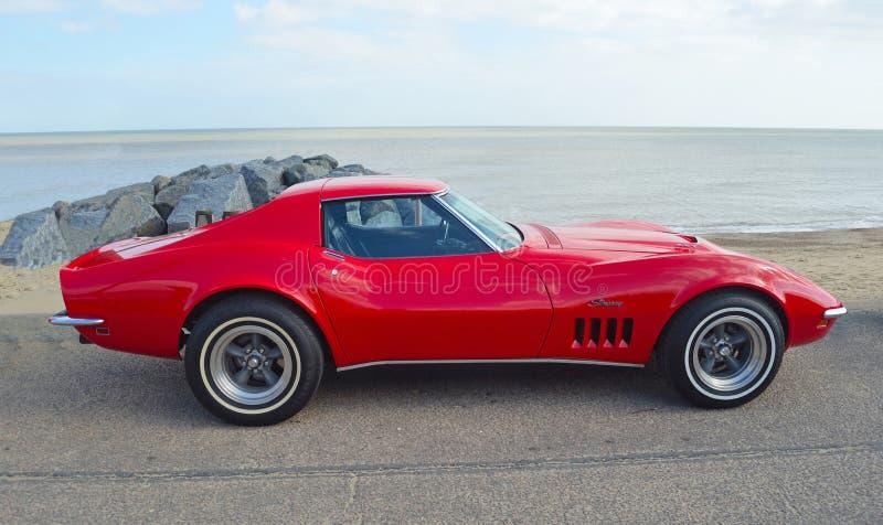 Carro vermelho clássico do motor da arraia-lixa de Chevrolet Corvette estacionado no passeio da frente marítima fotos de stock