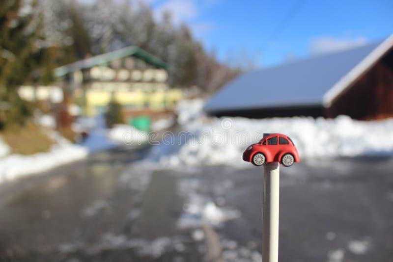 Carro vermelho do brinquedo em uma vara com a estrada nevado, gelada no inverno fotos de stock royalty free