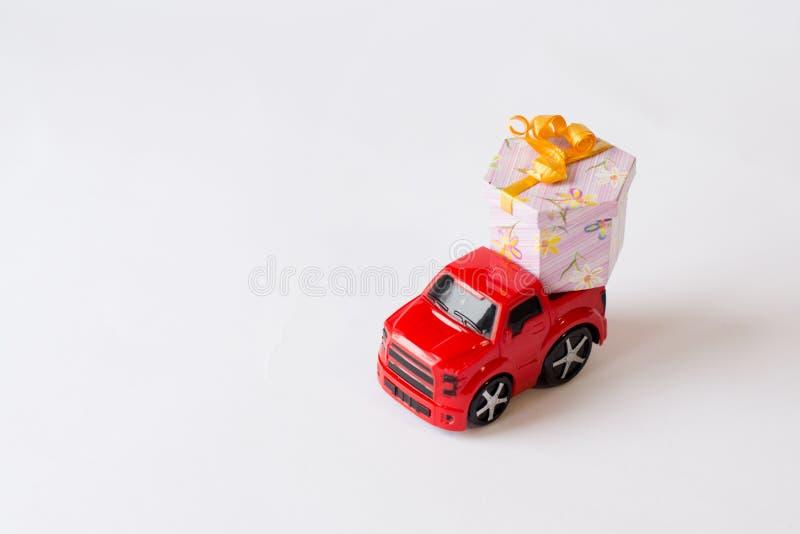 Carro vermelho do brinquedo que entrega a caixa de presente para o dia de são valentim no fundo branco celebration foto de stock