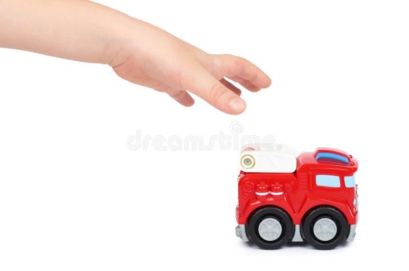 Carro vermelho do sapador-bombeiro do brinquedo com a mão da criança, isolada no fundo branco, motor do carro de bombeiros fotos de stock royalty free
