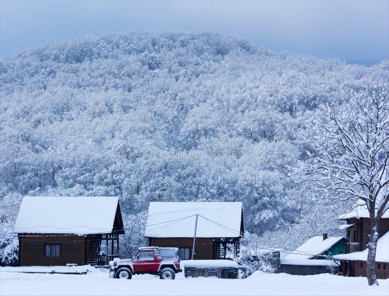 Carro vermelho do suv na neve perto de uma casa de madeira em um fundo de Forest Hills no tempo de inverno cedo na manhã imagem de stock