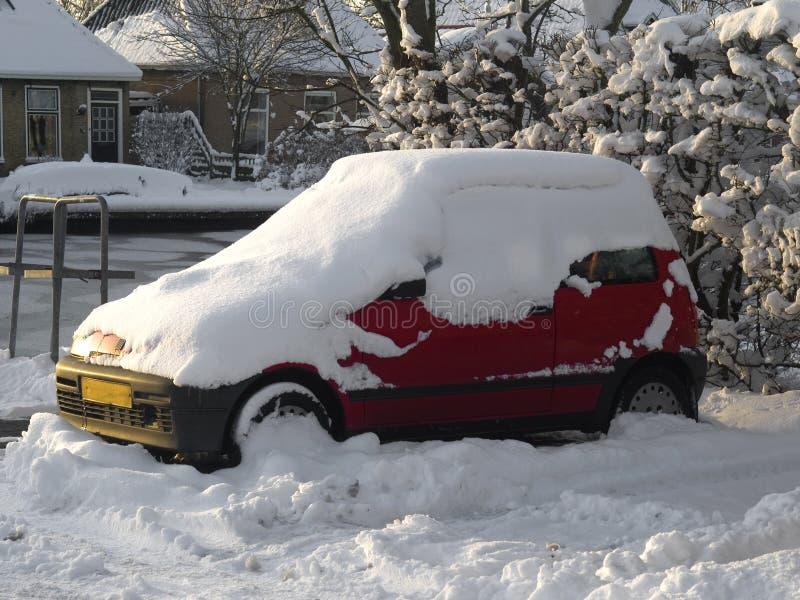 Carro vermelho estacionado sob uma camada de neve imagens de stock