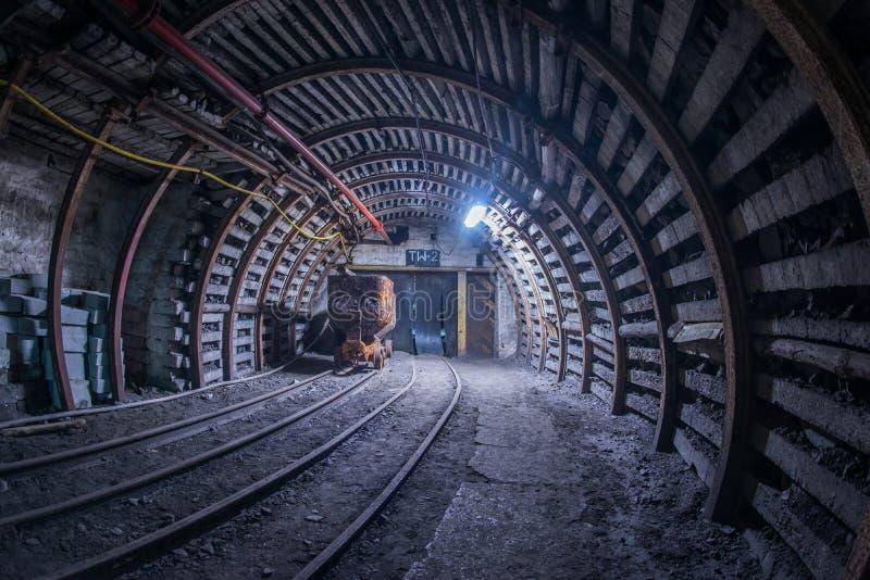 Carro viejo del carbón en pistas en los míos imagen de archivo