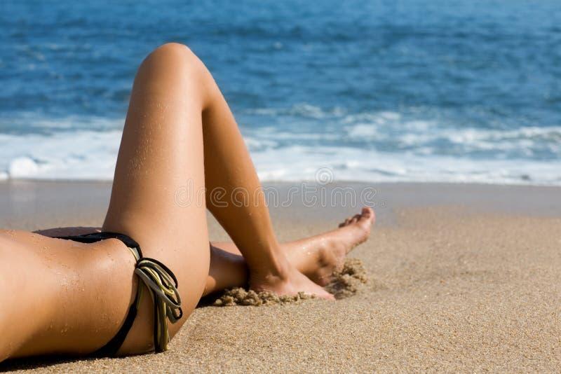 Carrocería de la muchacha que miente en la playa por el mar. fotografía de archivo
