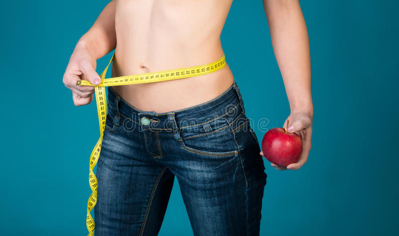 Carrocería femenina sana con la manzana y la cinta métrica Aptitud sana y consumición de concepto de la forma de vida fotos de archivo