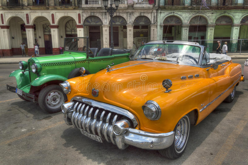Carros alaranjados e verdes na frente de Capitolio, Havana, Cuba imagens de stock