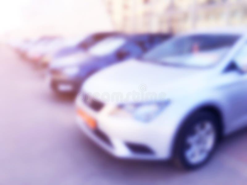Carros borrados no parque de estacionamento do carro no shopping Bokeh ilumina o fundo Parque de estacionamento abstrato do carro imagem de stock