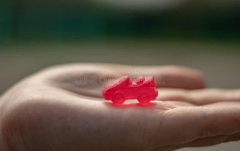 Carros comest?veis coloridos do doce de fruta em uma palma das crian?as Ideia do neg?cio para obter um empr?stimo da hipoteca ou  imagens de stock