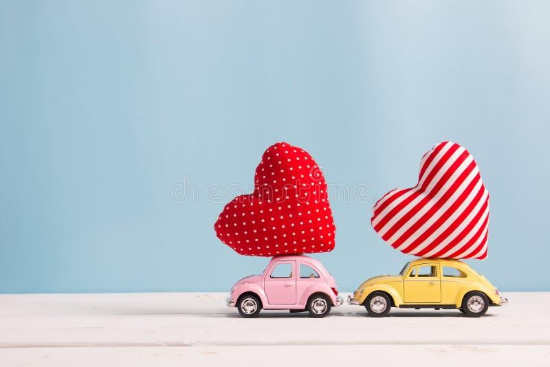 Carros cor-de-rosa e amarelos diminutos que levam coxins do coração imagens de stock royalty free