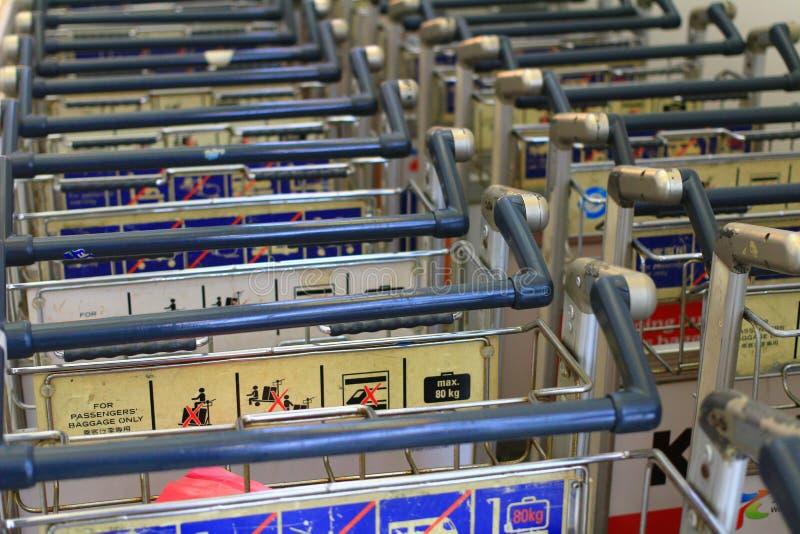 Carros del equipaje en el aeropuerto internacional moderno fotos de archivo