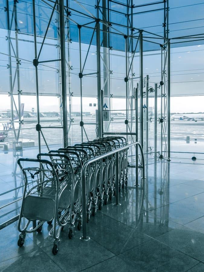Carros del equipaje en el aeropuerto moderno fotos de archivo