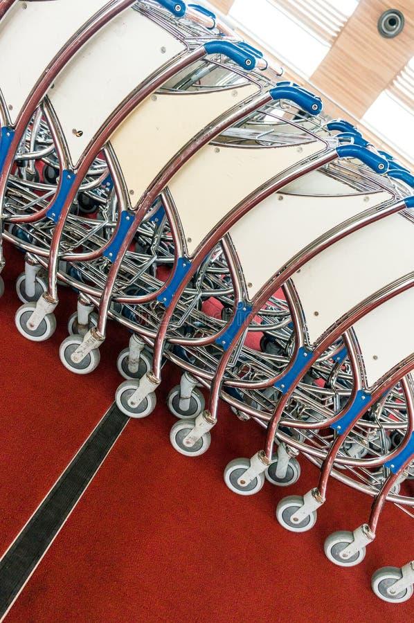 Carros del equipaje en el aeropuerto moderno foto de archivo
