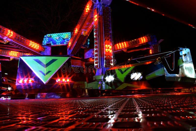 Carros del parque de atracciones en la noche imagenes de archivo