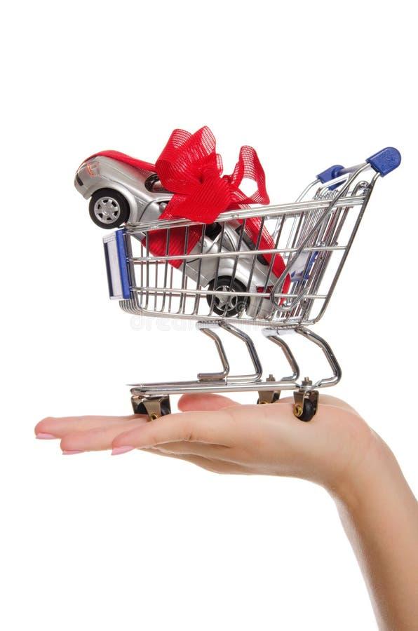 Carros e fita do presente no trole da compra na palma fotografia de stock royalty free