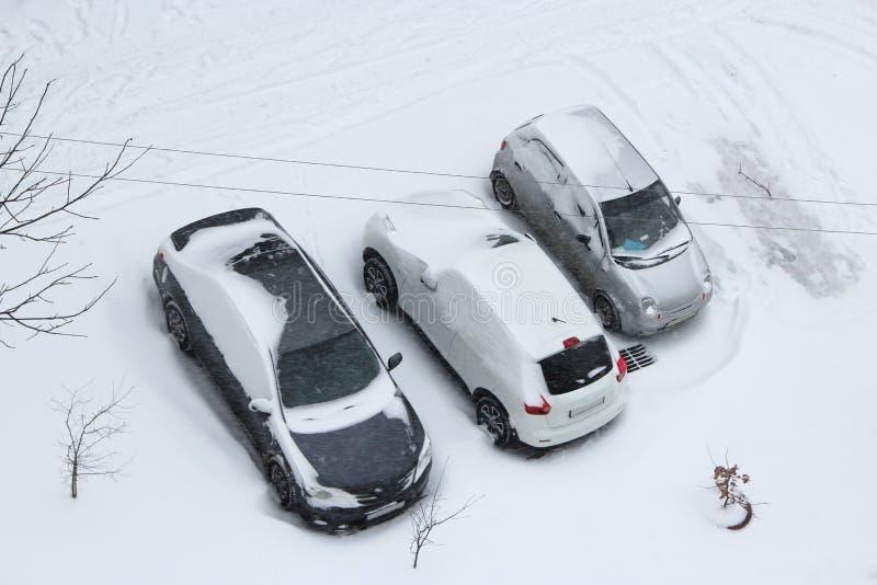 Carros estacionados cobertos com a neve Tempestade nevado Mau tempo na cidade cyclone fotografia de stock royalty free
