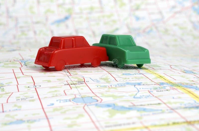 Carros plásticos diminutos em um mapa fotos de stock royalty free
