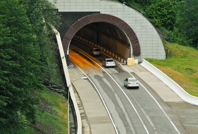Carros que movem-se para o túnel da estrada foto de stock