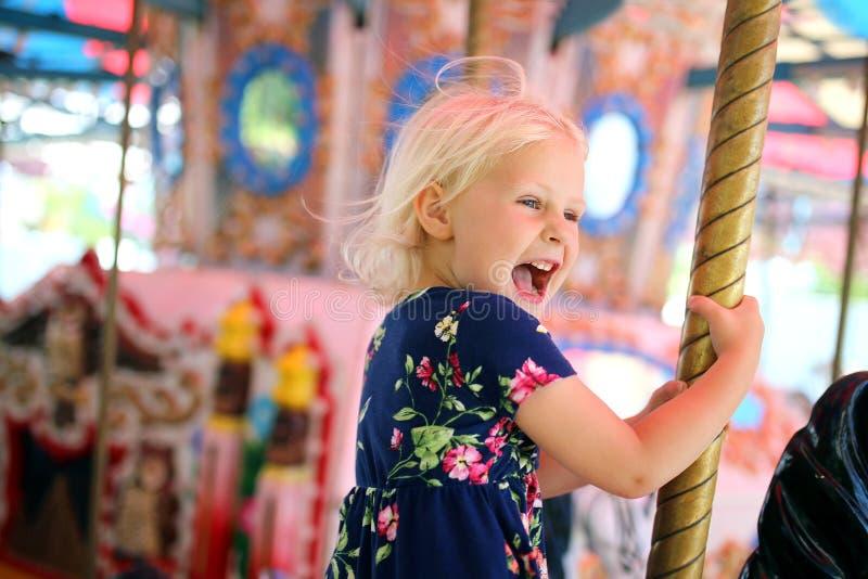 Carrossel feliz da equitação da criança no carnaval imagem de stock