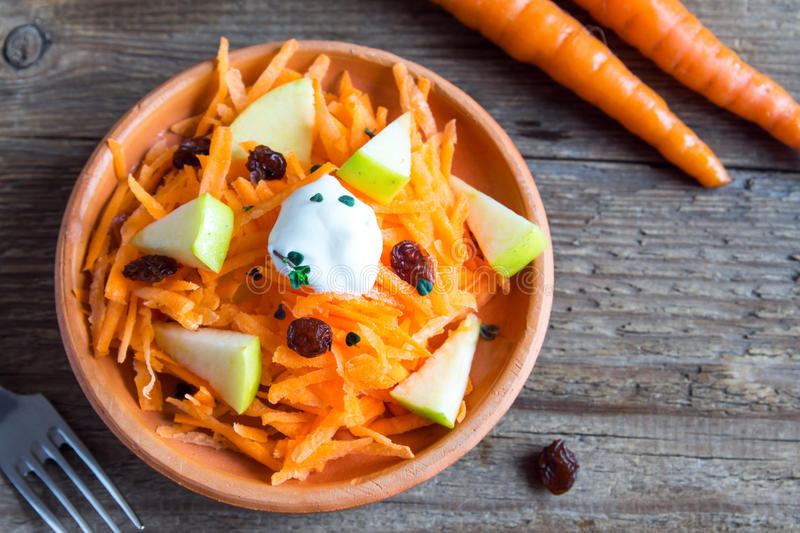 Carrot and apple salad with raisins. Yogurt and herbs in rustic ceramic bowl, copy space royalty free stock photography