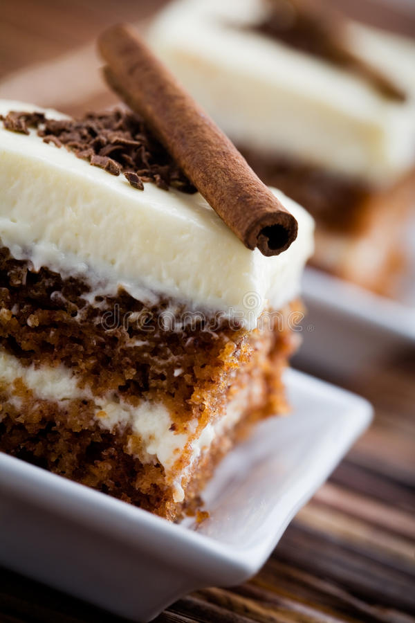 Carrot cake. Delicious pieces of carrot cake with cinnamon stick royalty free stock photo