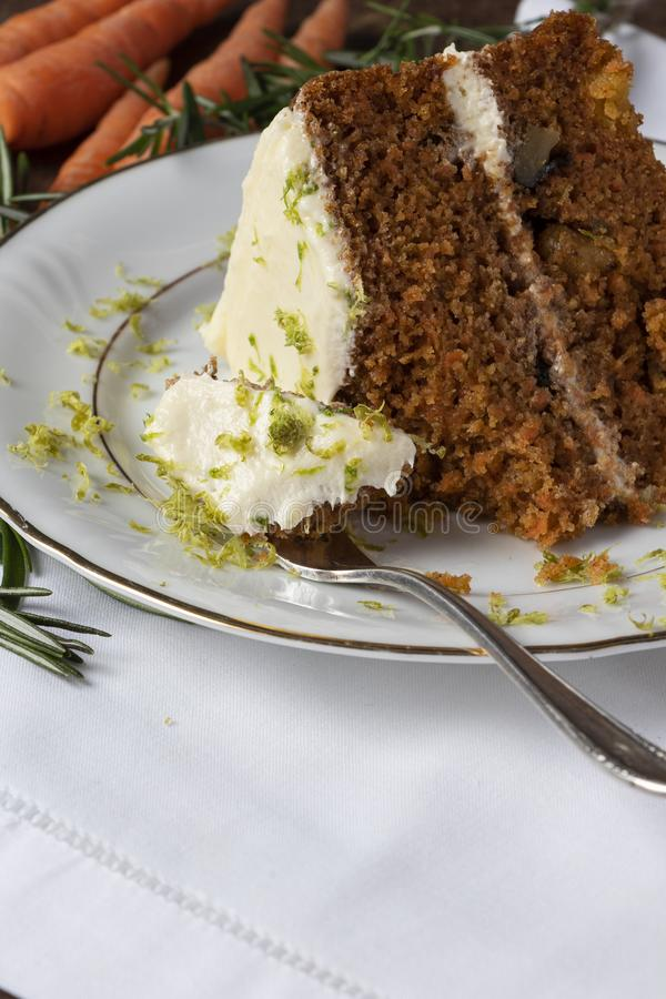 Carrot cake and grated lemon. Portion for a person with a fork. Sweet moment in celebration. stock photos