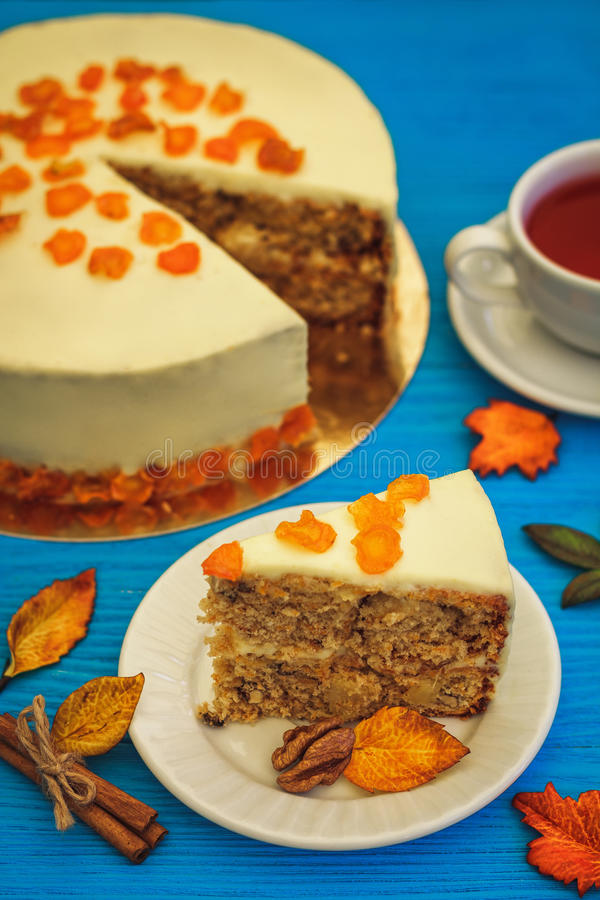 Carrot cake with red tea on blue background royalty free stock photo