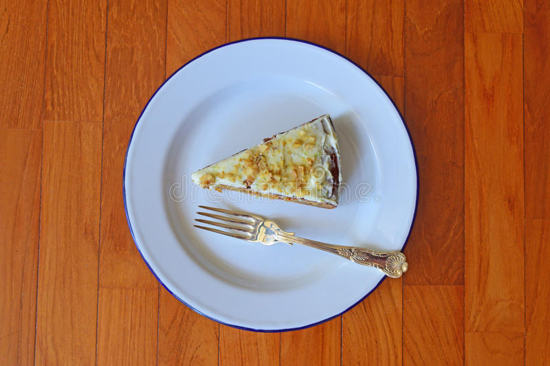 Carrot cake served on classic enamelware with silver spoon stock image